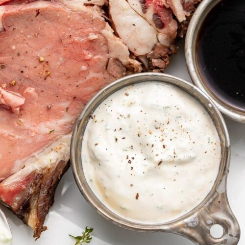 A side of horseradish sauce next to prime rib on a white plate