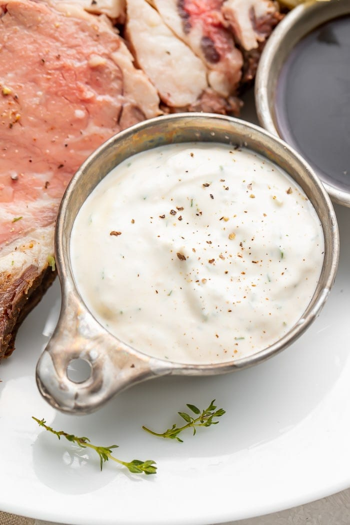 Close up of a silver dish with horseradish sauce next to prime rib on a plate
