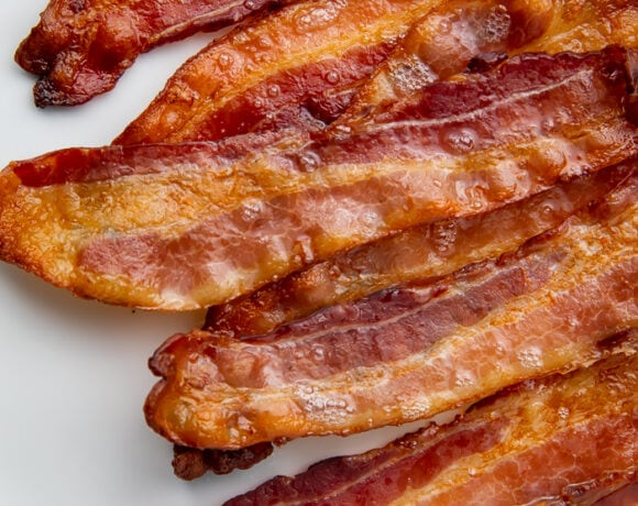 White serving plate with slices of crispy bacon