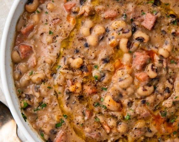 White bowl holding instant pot black eyed peas with ham, bacon, and onion