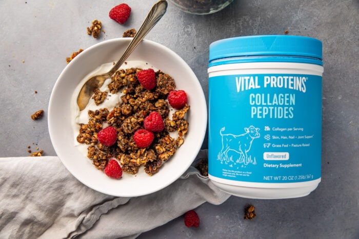 Vital proteins collagen peptides container next to a bowl of yogurt topped with granola and raspberries
