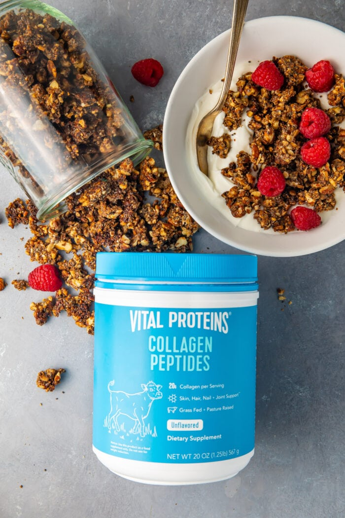 Vital Proteins collagen peptides container next to a glass jar of spilled granola and a bowl of keto granola on top of yogurt with raspberries