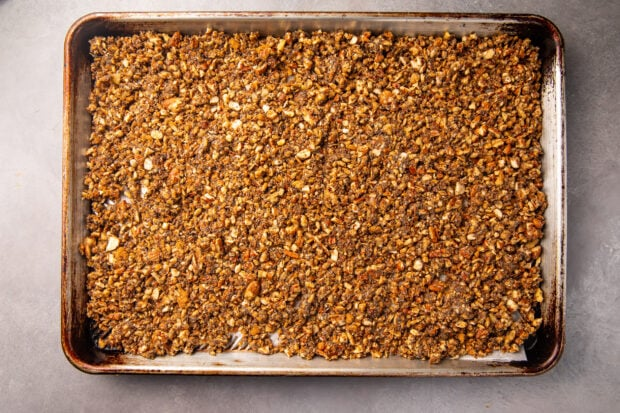 Unbaked keto granola spread out on a baking sheet