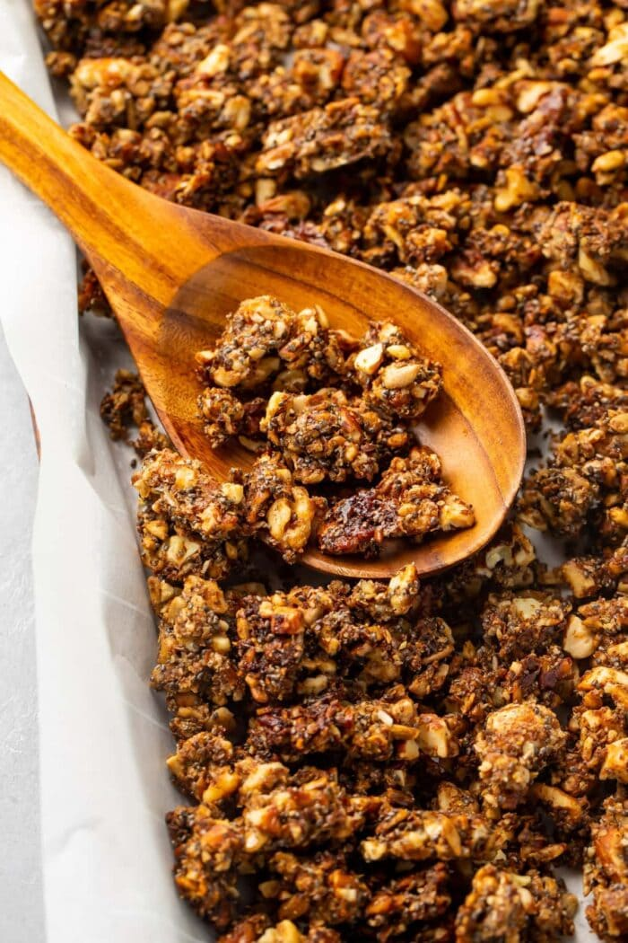 Baked keto granola on a sheet pan with a wooden spoon
