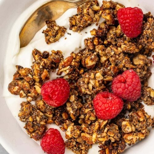 Keto granola on top of a bowl of yogurt garnished with raspberries