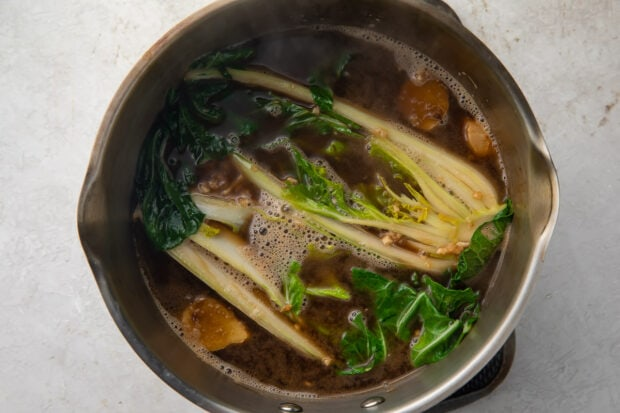 Ramen broth and bok choy in a silver pot