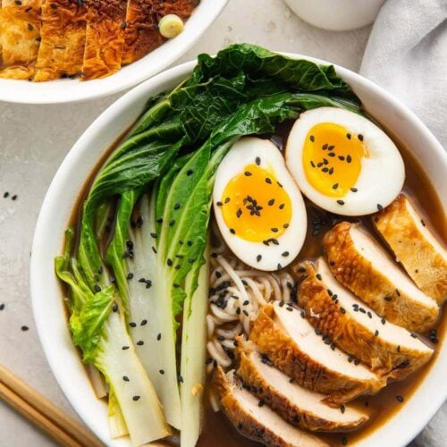 A white bowl of keto ramen with shirataki noodles, ramen eggs, chicken, and bok choy