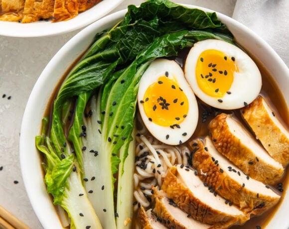 A white bowl of keto ramen with shirataki noodles, ramen eggs, chicken, and bok choy