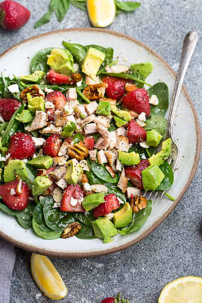Strawberry avocado spinach salad on a white plate with a fork