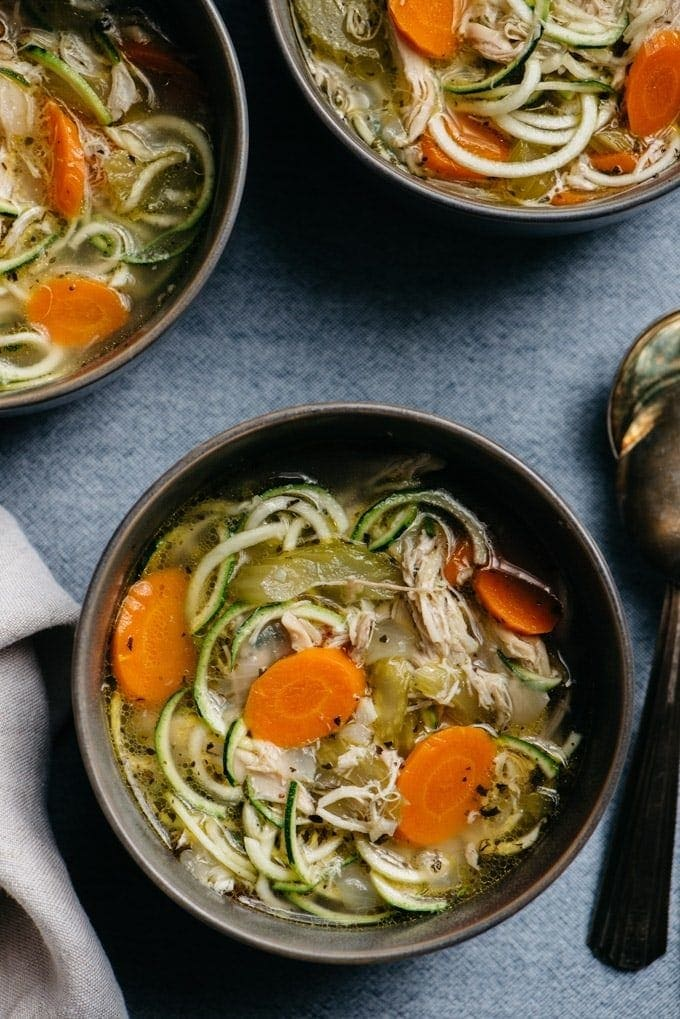 Whole30 chicken zoodle soup in a black bowl
