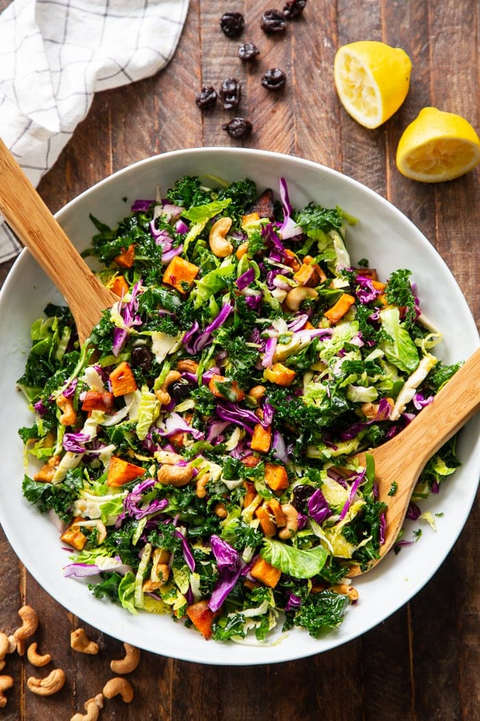 Rainbow veggie salad in a skillet with two wooden spoons