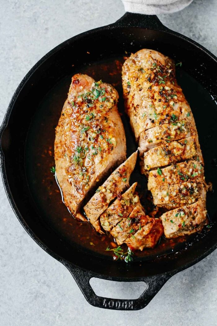 Cast iron pan holding two large pork tenderloins marinated in garlic butter and seasonings