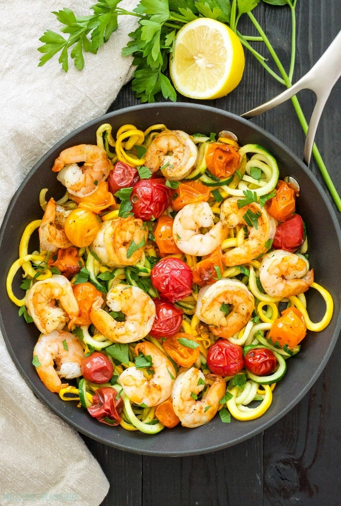 Cast iron skillet with zucchini zoodles, shrimp, and roasted tomatoes, garnished with lemon