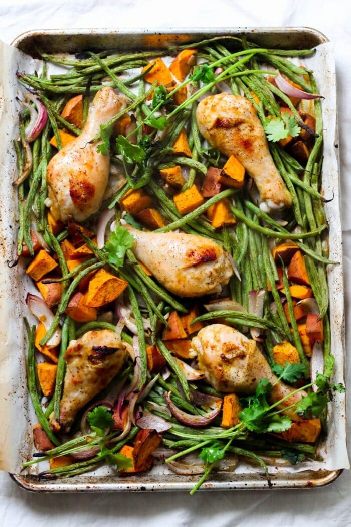 Chicken drumsticks and green beans on a sheet pan