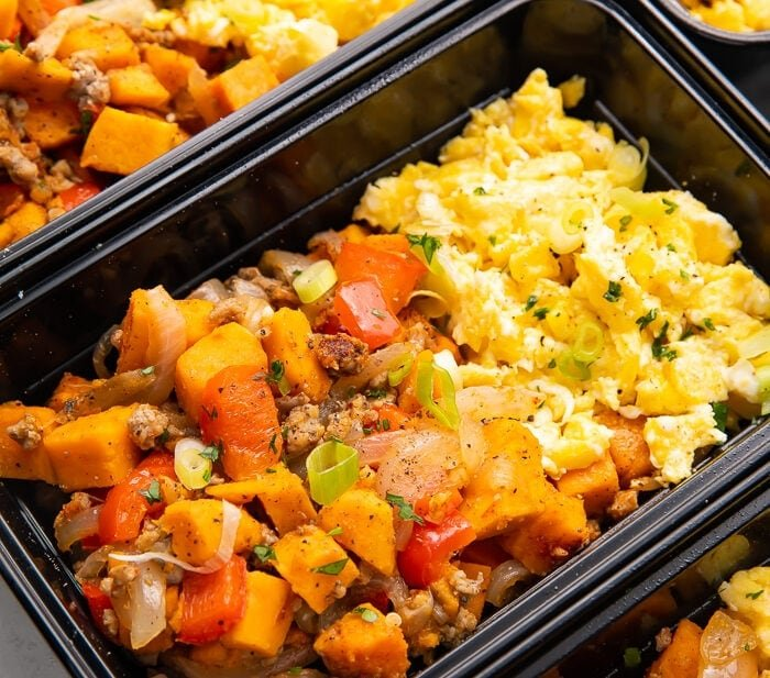 Reusable meal prep trays with sweet potato, scrambled eggs, and sausage for a whole30 breakfast