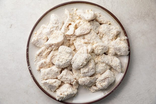 Flour coated chicken breast chunks on a white plate with brown edges