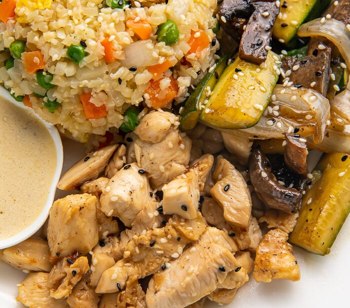 Close up photo of whole30 hibachi chicken, rice, and veggies on a white plate