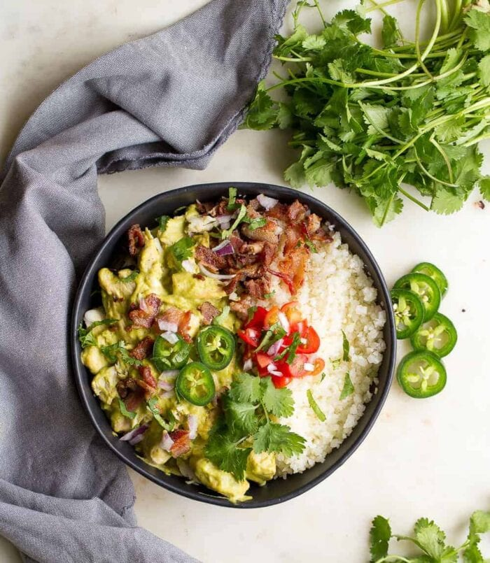 A black bowl containing jalapenos, chicken, and cauliflower rice on a white table surrounded by jalapenos