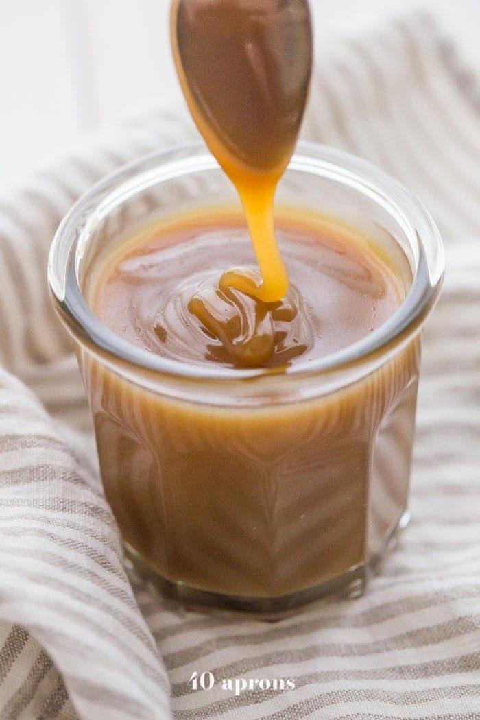 Vegan Instant Pot caramel sauce drizzling off a spoon into a glass jar of caramel sauce