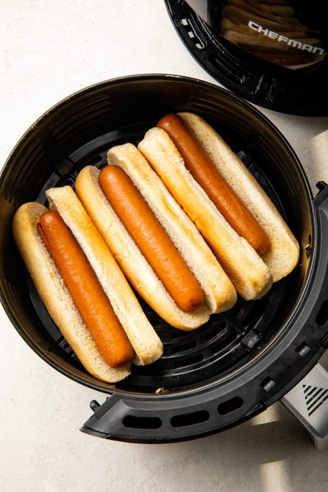 3 Hot dogs in buns in an air fryer basket