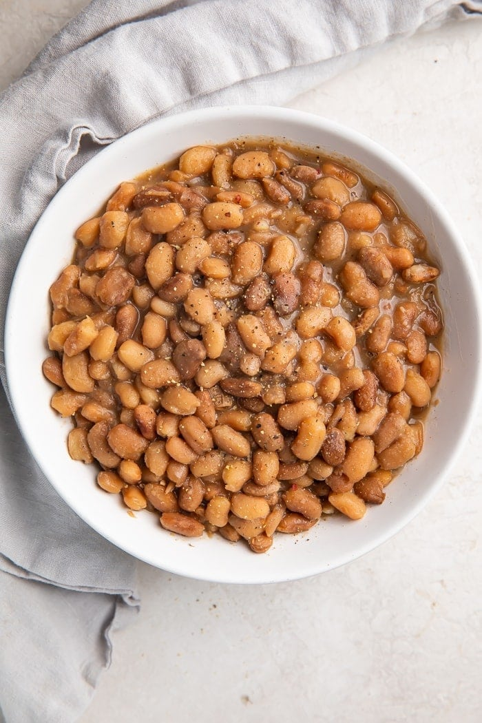 Zoomed out overhead photo of vegan Instant Pot pinto beans in a white bowl on a marble countertop