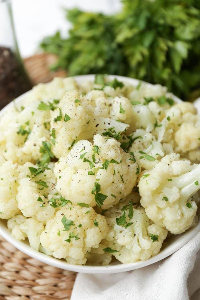 A white bowl of cauliflower florets with garnish
