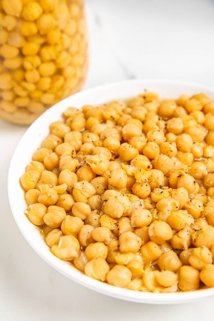 A partial bowl of chickpeas next to a jar of chickpeas on a white background