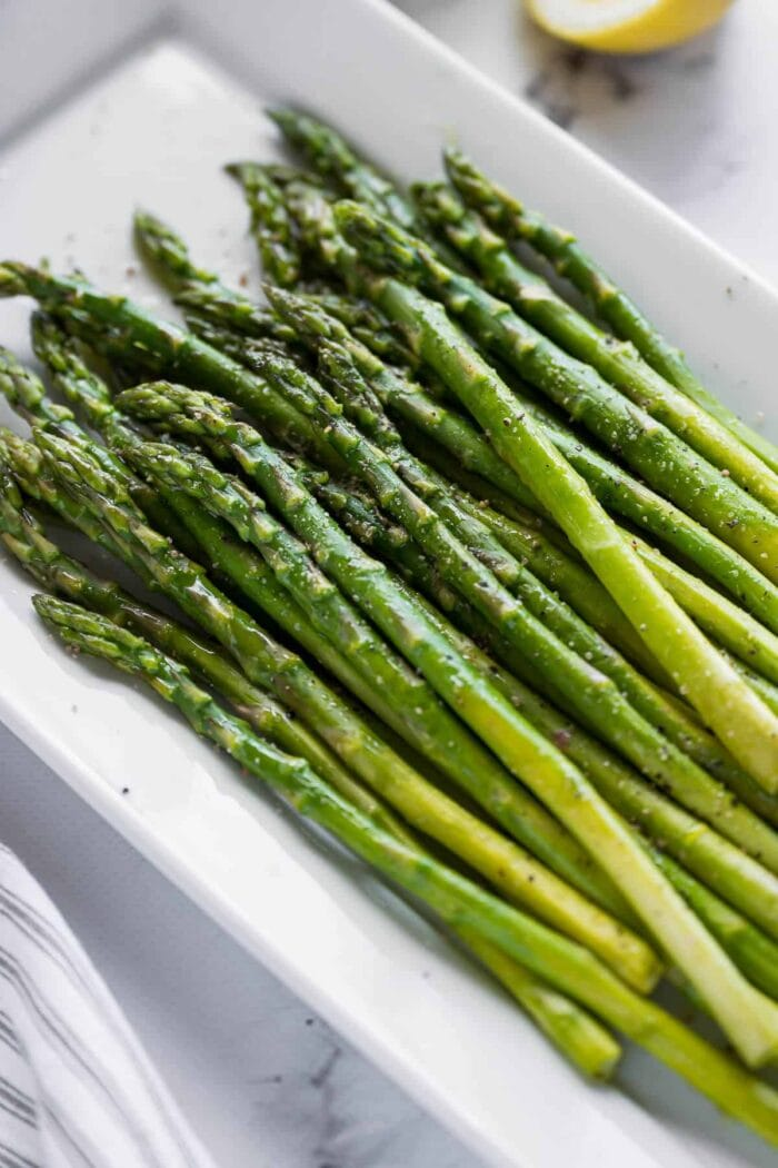 A white platter holding cooked asparagus stalks