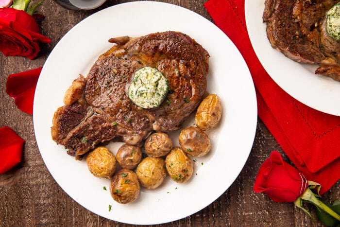 Whole bone-in ribeye with garlic-herb butter on a white plate with whole roasted potatoes surrounded by red roses and a red napkin on a wooden table