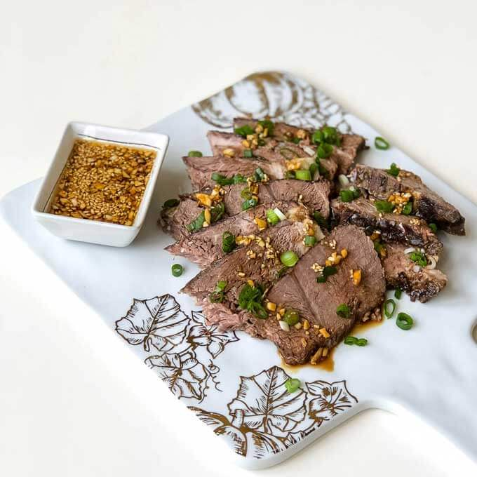 A marble platter with sesame beef and a square bowl of dipping sauce