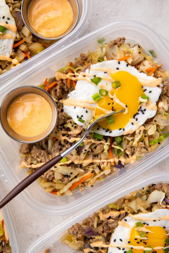 Egg roll in a bowl with a fried egg in meal prep containers