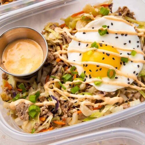 Close up of Egg roll in a bowl with a fried egg in meal prep containers