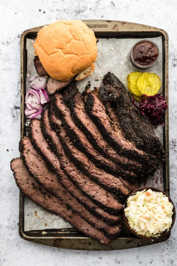 Sliced brisket on a sheet pan with bread and garnish