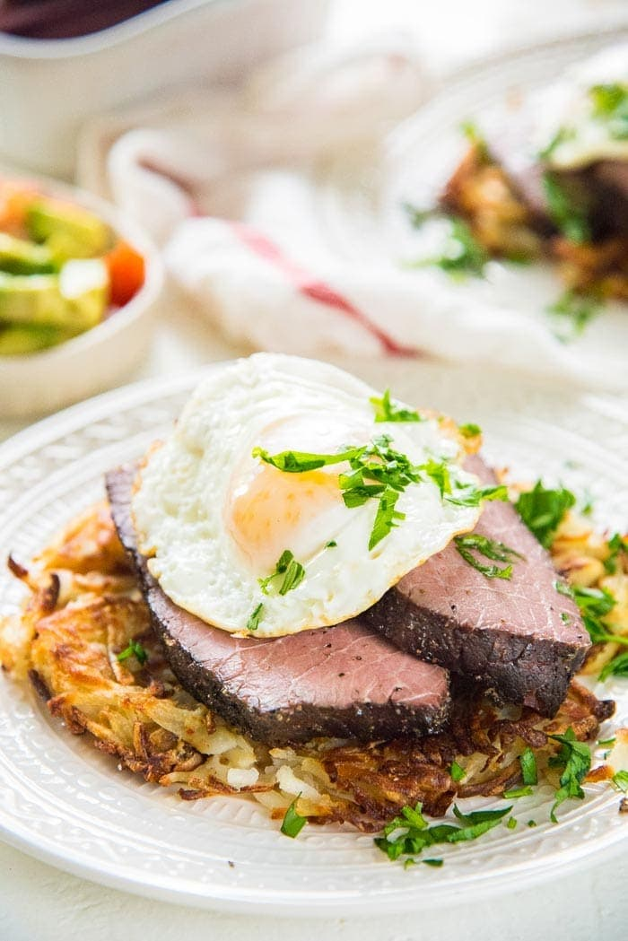Sous vide rump roast on a white plate topped with a fried egg