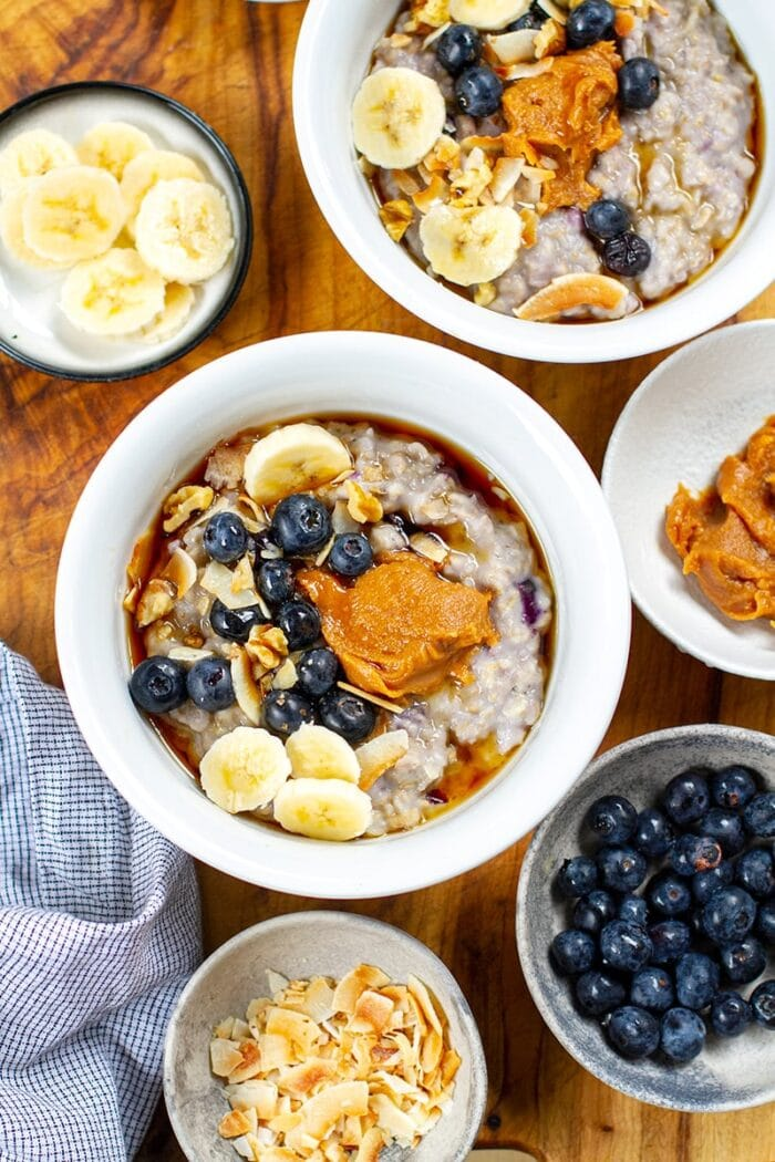 Two bowls of oatmeal with blueberries, peanut butter, and maple syrup