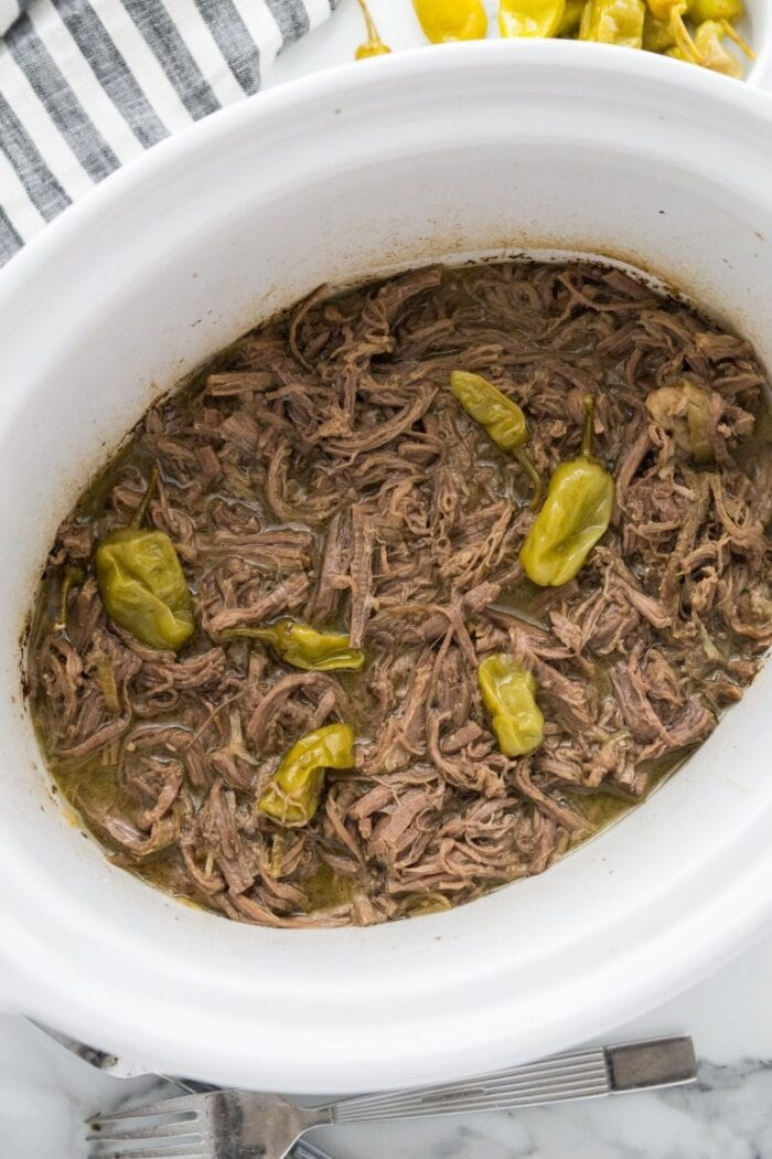 Slow cooker pot roast in a white slow cooker dish