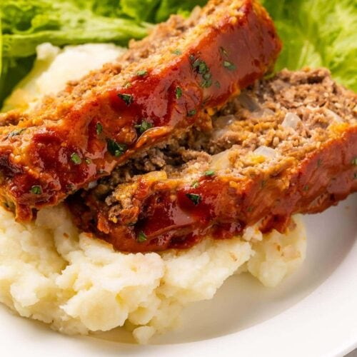 Two slices of keto meatloaf plated on mashed cauliflower with a romaine lettuce garnish