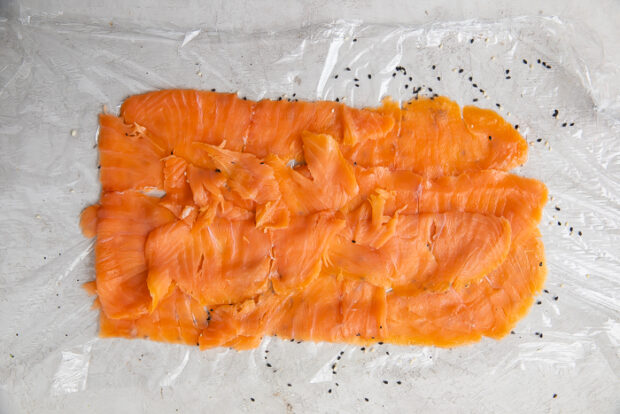 Thinly sliced salmon arranged in a large rectangle on a sheet of plastic wrap