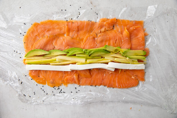 Cream cheese, avocado, and cucumber arranged on top of salmon and sesame seeds on a sheet of plastic wrap