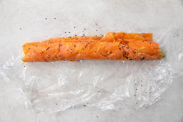 Salmon sushi roll on plastic wrap