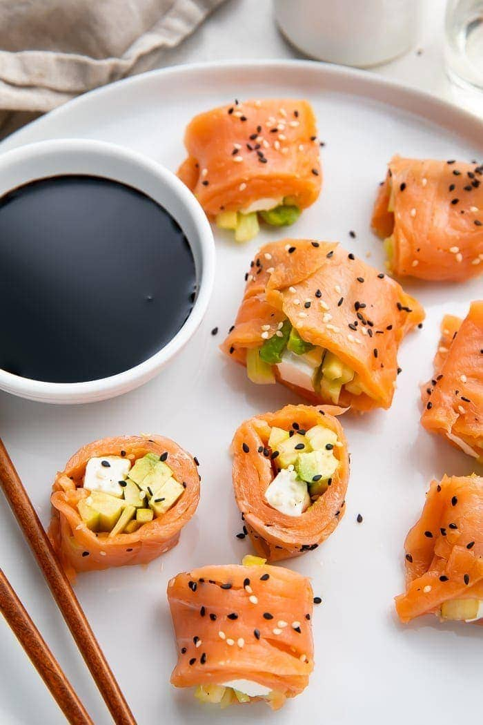 8 pieces of keto smoked salmon sushi on a white plate with chopsticks next to a bowl of soy sauce