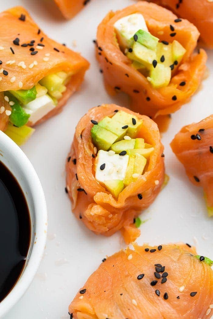 Several pieces of keto smoked salmon sushi next to a bowl of soy sauce