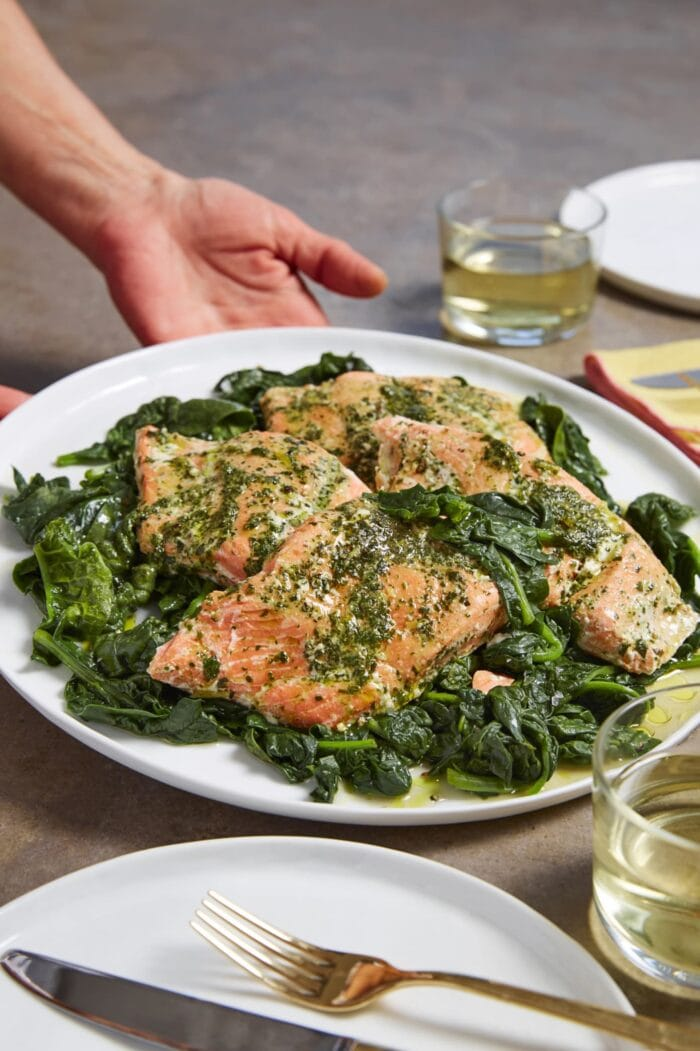 Sous vide salmon in herb butter on a plate of spinach
