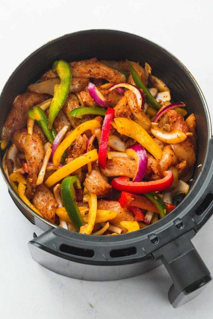 Keto chicken fajitas and peppers in an air fryer basket