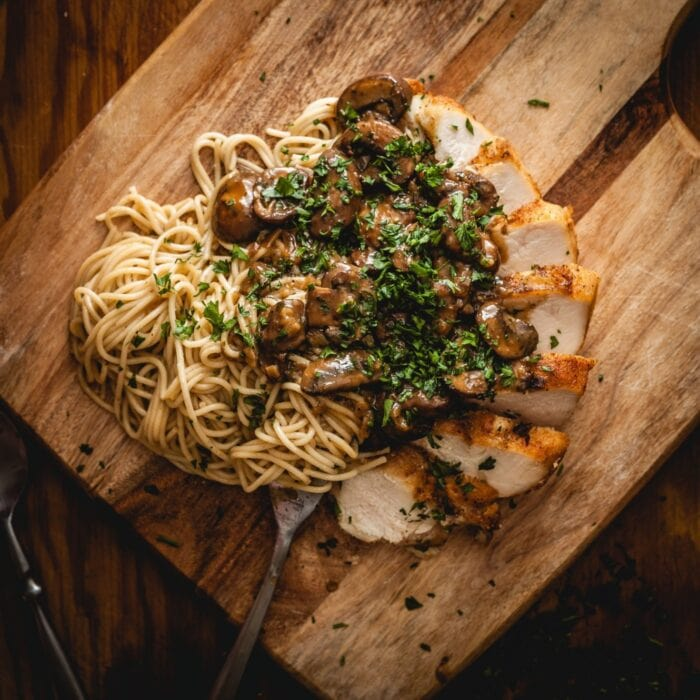 Closeup of pasta, chicken marsala, and mushrooms on a cutting board