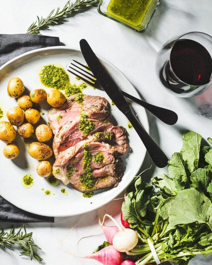 Plated leg of lamb with potatoes, lettuce, and black silverware