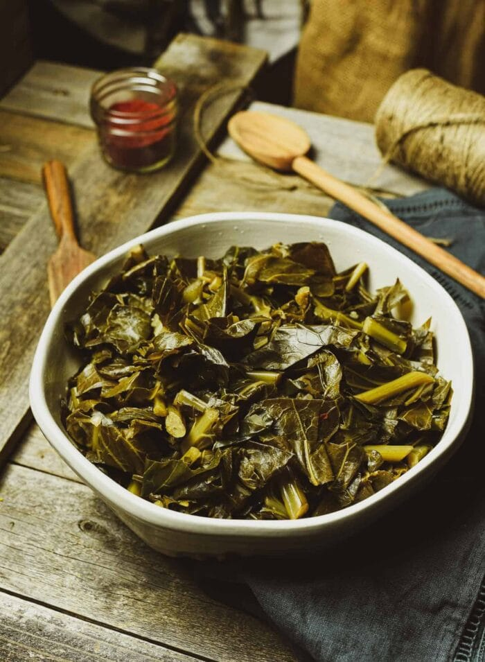 Vegan Instant Pot collard greens in a funky sage bowl with a wooden spoon on a wooden table
