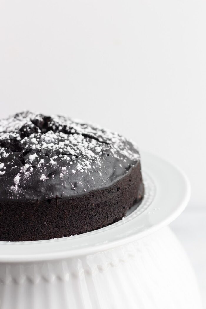Half of a vegan chocolate cake on a white cake stand with a white background