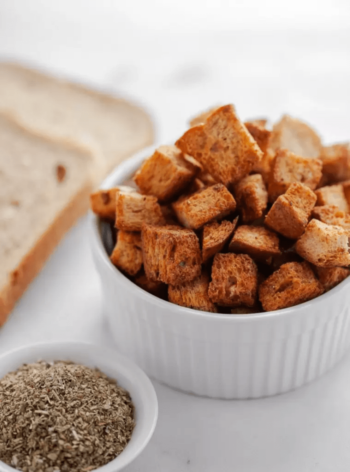 A white bowl of air fried croutons next to a slice of keto bread