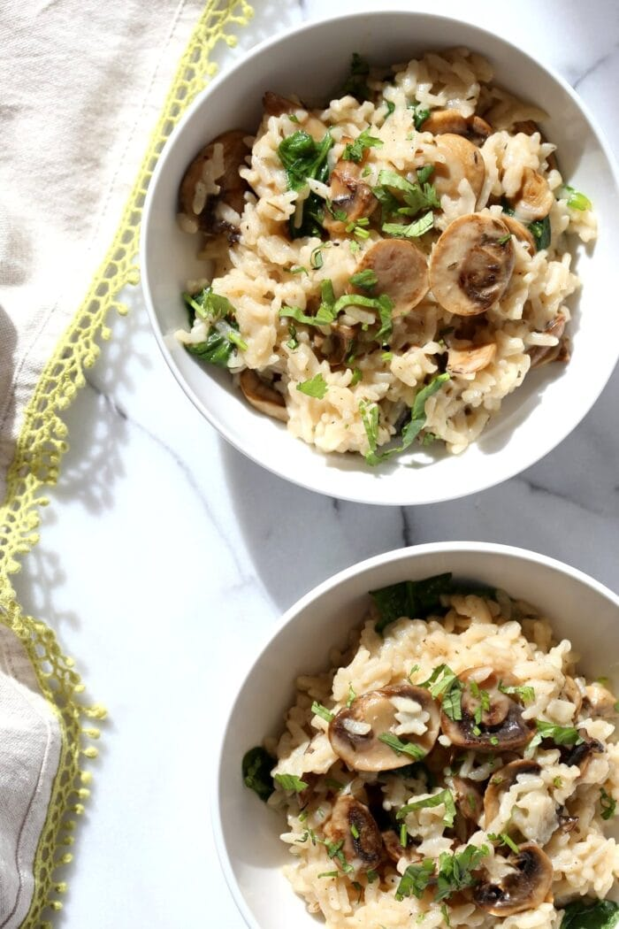 One and a half bowls of mushroom risotto on a white table